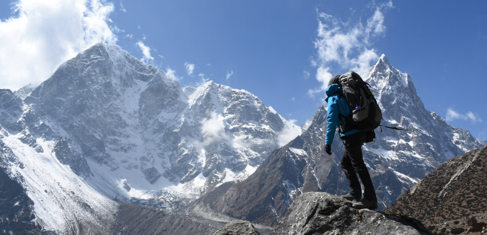Trekker on the Everest Base Camp Trek in front of Mount Cholache and Mount Tabuche